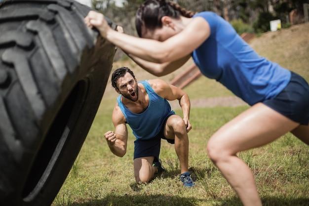 Fit frau, die einen reifen umdreht, während trainer während des hindernislaufs im bootcamp jubelt