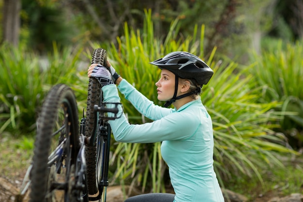 Fit frau, die fahrradreifen repariert