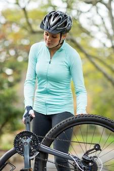 Fit frau, die ihr fahrrad repariert