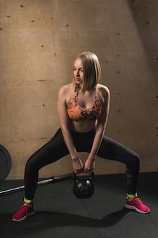 Fit frau, die schwere kesselglocke im fitnessstudio hebt