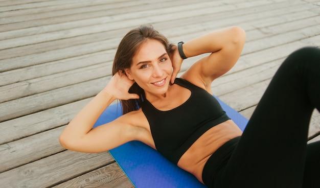 Fit frau, die seitliche drehübungen für bauchmuskeln macht