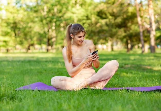 Fit frau, die yoga macht und online-tutorials auf dem smartphone sieht