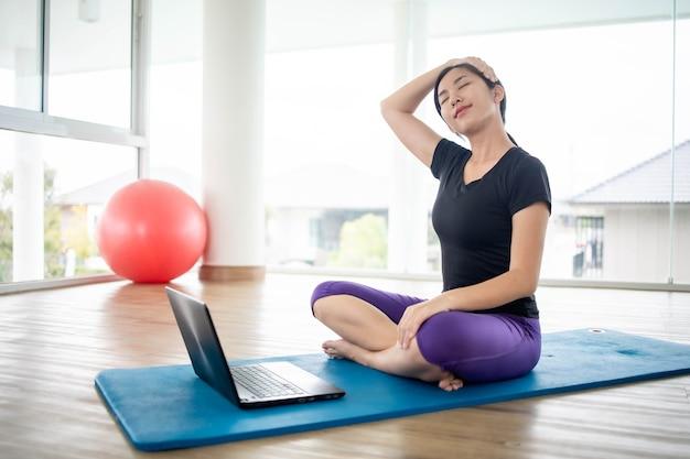 Fit frau, die yoga macht und online-tutorials auf notizbuch sieht