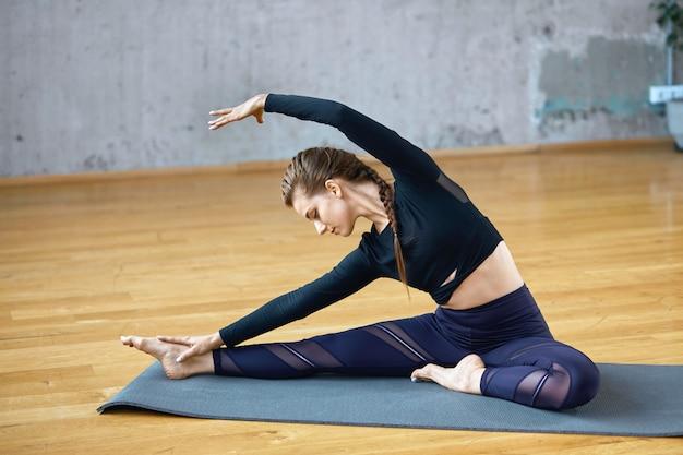 Fit frau, die yoga seite biegeübung übt.