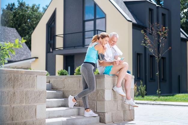 Fit frau. fit frau trägt graue leggings und weiße turnschuhe, die in der nähe ihres athletischen mannes stehen, nachdem sie erstaunlichen sportmorgen hatten