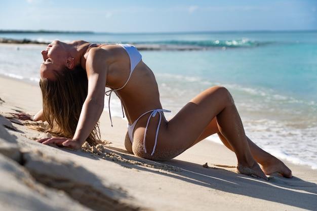 Fit frau im weißen bikini, der am strand sitzt und sonnenbad, weißen sand und klares azurblaues meerwasser genießt