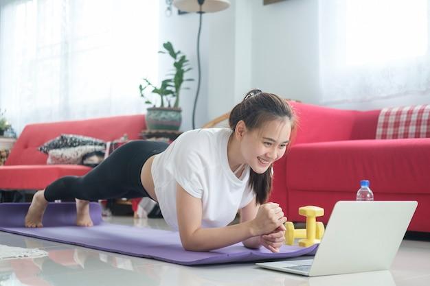 Fit frau macht yoga-planke und sieht online-tutorials, training im wohnzimmer. bleib zu hause lebensstil.