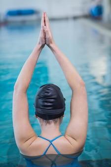 Fit frau mit erhobenen armen im pool