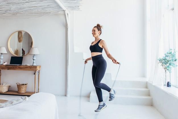 Fit frau mit springseil zu hause beim überspringen des trainings.