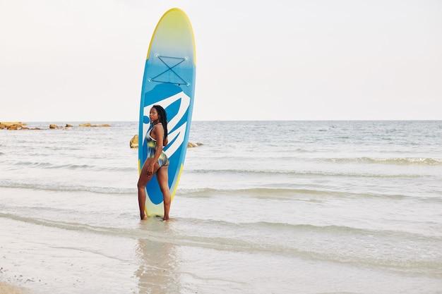 Fit frau mit sup surfbrett