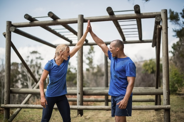 Fit frau und mann geben sich während des hindernislaufs im bootcamp einen high five