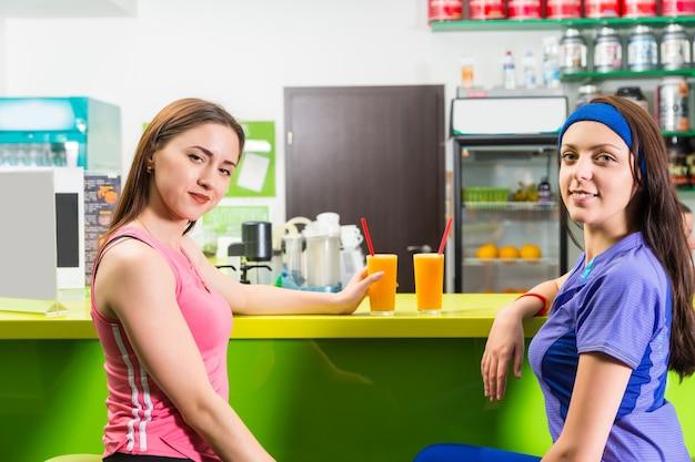 Fit frauen entspannen sich bei einem drink im fitnessstudio und genießen einen gesunden energy-drink