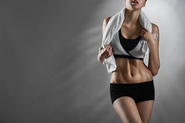 Fit fühlen. weibliche fitnesstrainerin, die sportkleidung trägt und mit einem handtuch um den hals auf blauem hintergrund posiert, der kopienraum auf der seite wegschaut