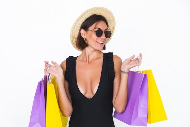 Fit gebräunte frau in schwarzer badeanzug-sonnenbrille und strohhut auf weißen einkaufstüten glücklich positiv fröhlich