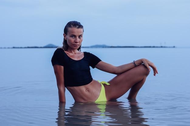 Fit gebräunte junge kaukasische frau im meer bei sonnenuntergang