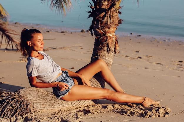 Fit gebräunte schlanke frau in top und shorts am tropischen strand bei sonnenuntergang
