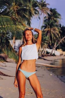 Fit gebräunte schlanke kaukasische frau im weißen oberteil und im blauen höschen bei sonnenuntergang am tropischen strand. gebräunte frau in guter form, die sonne und ozean genießt