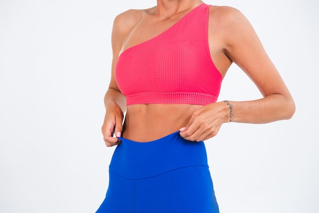 Fit gebräunte sportliche frau mit bauchmuskeln, fitnesskurven, trägt top und blaue leggings auf weiß