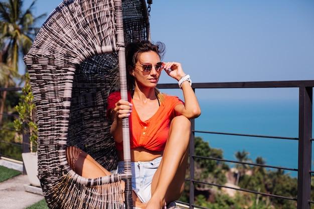 Fit gebräunte tätowierte kaukasische europäische frau mit sportkörper und bauchmuskeln, in jeansshorts und rotem orangefarbenem hemd