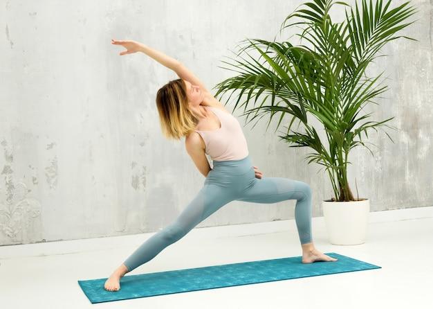 Fit geschmeidige frau, die eine reverse warrior yoga-pose macht, um ihre kernmuskeln zu stärken und die flexibilität zu erhöhen