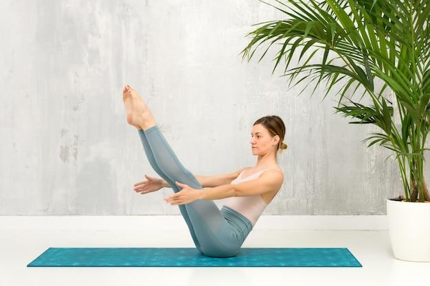 Fit gesunde frau, die eine navasana yoga pose oder boat pose macht, um die wirbelsäule zu stärken und zu dehnen