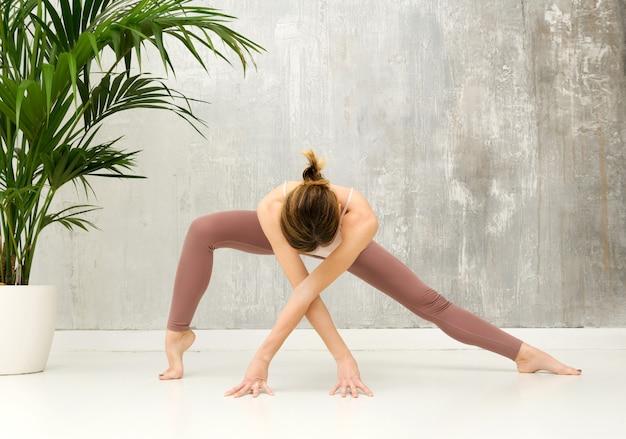 Fit gesunde frau, die eine parighasana variation yoga-pose mit breitem bein streckt, um ihre hüftbeuger zu stärken
