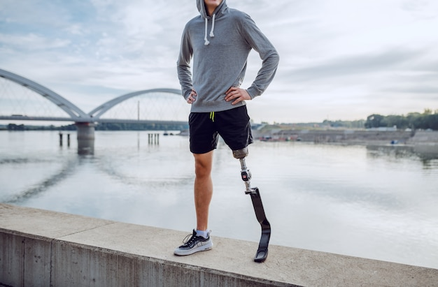 Fit gesunden kaukasischen behinderten mann in sportbekleidung und mit künstlichem bein auf kai mit den händen auf den hüften stehen.