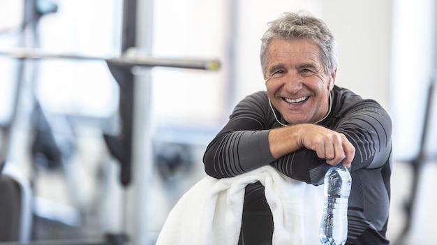 Fit in seinen sechzigern, mann ruht auf einem handtuch lächelnd in der turnhalle.
