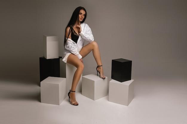 Fit junge brünette weibliche t-shirt mit nackten beinen sitzen auf schwarzen und weißen würfeln auf grauem hintergrund, kopienraum. foto in hoher qualität