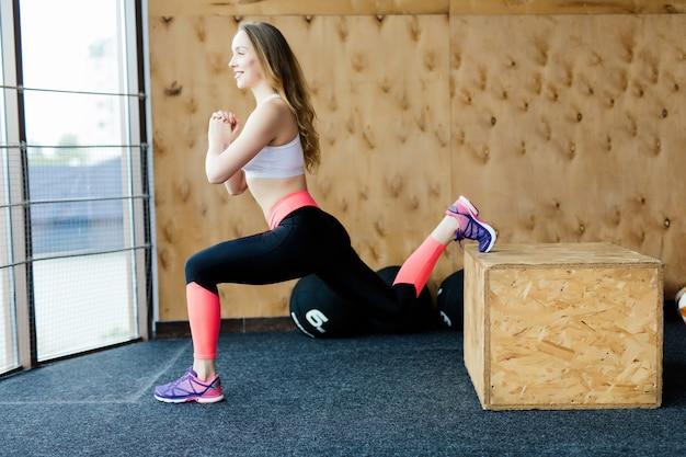 Fit junge frau box jumping in einem crossfit-stil fitnessstudio. sportlerin führt boxensprünge im fitnessstudio durch.
