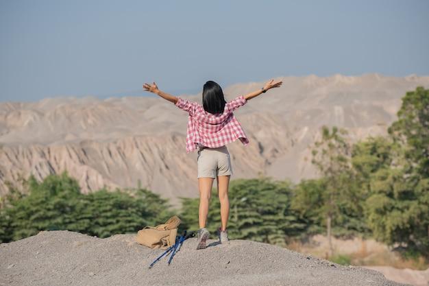 Fit junge frau, die in den bergen steht, die auf einem felsigen gipfelgrat mit rucksack und stange stehen, die über landschaft schauen.