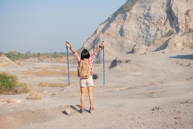 Fit junge frau, die in den bergen wandert, die auf einem felsigen gipfelgrat mit rucksack stehen