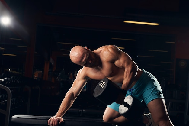 Fit junger männlicher sportler, der hart arbeitet, während er im fitnessstudio trainiert