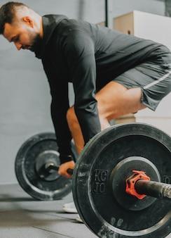 Fit junger mann in sportbekleidung, die vorbereitet, gewichte während einer trainingseinheit in einem fitnessstudio zu heben. fitness-sport oder gesundes lifestyle-konzept.