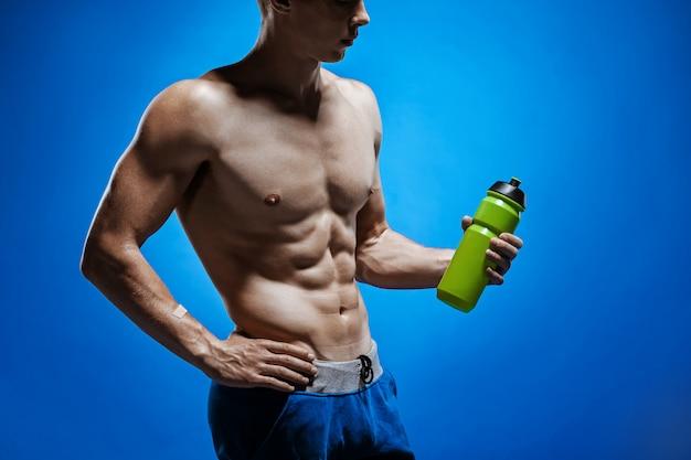 Fit junger mann mit schönem torso auf blauem hintergrund