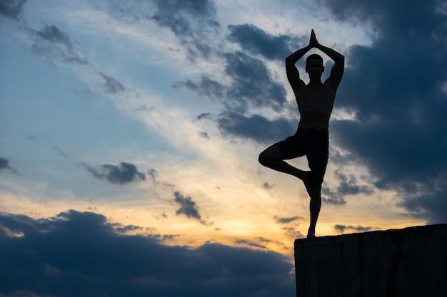 Fit junger mann praktiziert sonnengruß yoga am rande der klippe bei sonnenuntergang.