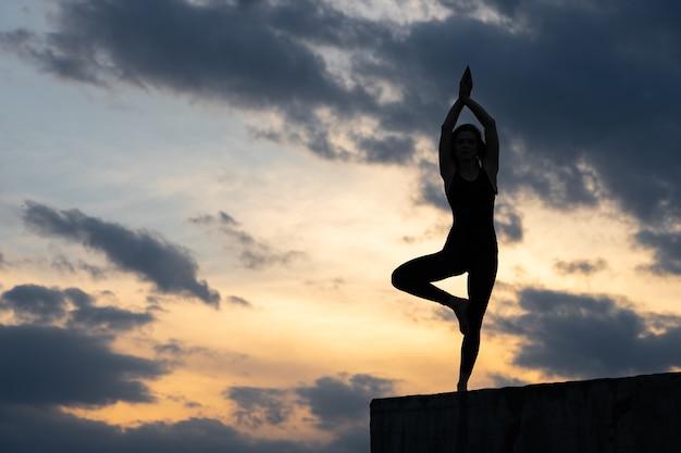 Fit junges mädchen praktiziert sonnengruß yoga am rande der klippe bei sonnenuntergang.