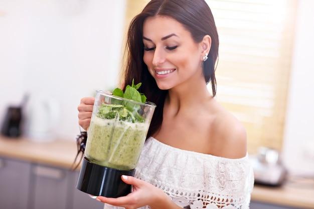 Fit lächelnde junge frau, die einen gesunden smoothie in der modernen küche zubereitet