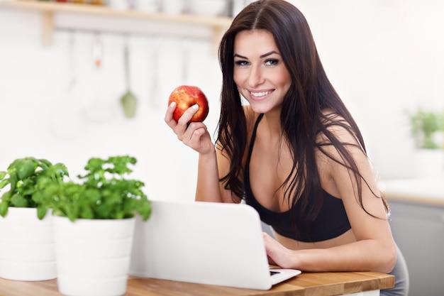 Fit lächelnde junge frau mit apfel in der modernen küche