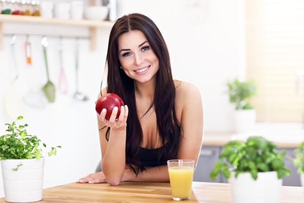 Fit lächelnde junge frau mit gesundem saft in der modernen küche