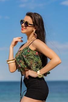 Fit mädchen in trendigen coolen sonnenbrillen mit hellbraunem körper posiert am tropischen strand und trägt ein farbenfrohes oberteil, hohe shorts und stilvolle beute-accessoires.