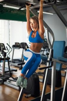 Fit mädchen training bauchmuskeln durch anheben der beine auf einem horizontalen balken.