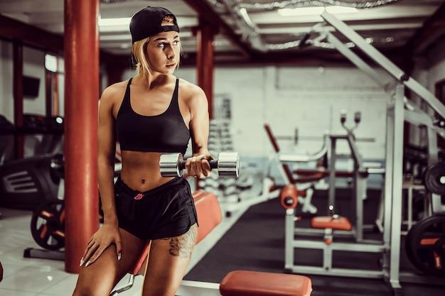 Fit mädchen übung mit hanteln im fitnessstudio.