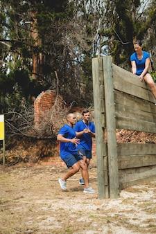 Fit männer klettern eine holzwand während des hindernislaufs