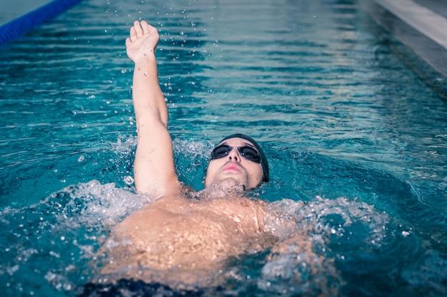 Fit mann auf dem rücken im pool schwimmen