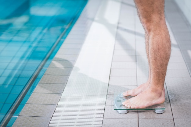 Fit mann auf waage am pool