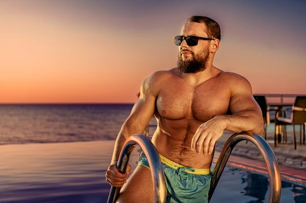 Fit mann bodybuilder aus dem pool kommen