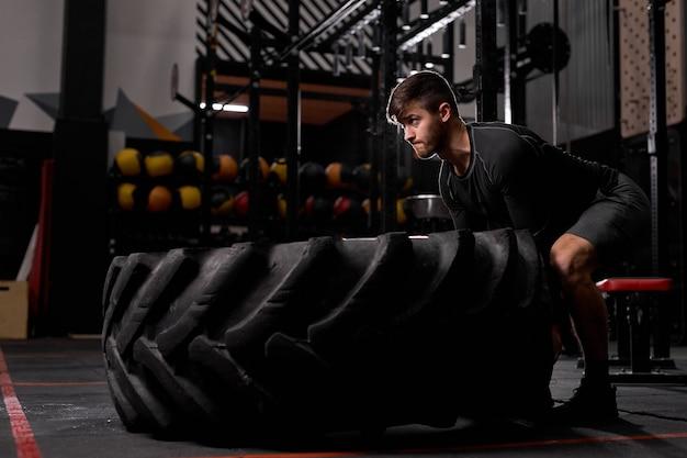 Fit mann dreht den reifen, cross-fit-funktionssport im fitnessstudio. mann, der mit radsportarten trainiert, mit cross fit beschäftigt. sportkonzept