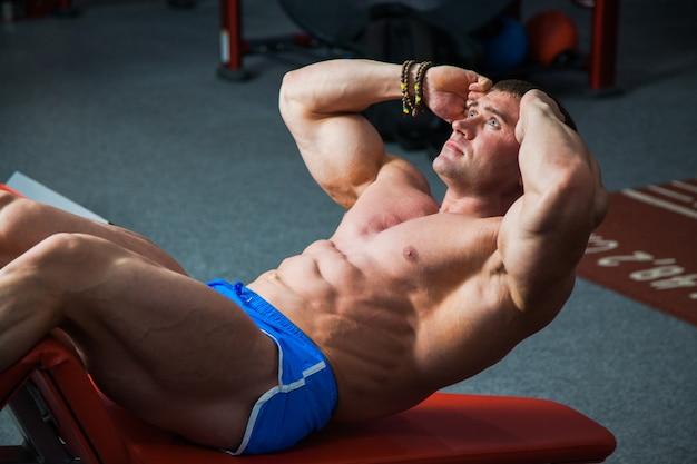 Fit mann heben torso trainieren bauchmuskeln training im fitnessstudio. junge bodybuilder machen bauchmuskelübungen mit sportgeräten