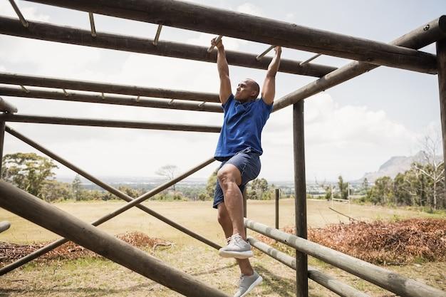 Fit mann klettern kletterstangen während hindernislauf im bootcamp